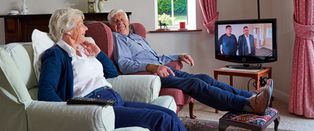 Image of two people aged over 75 watching television